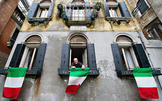 VENICE, ITALY - MARCH 16: A man hangs an Italian National Flags outside his window ahead of the celebrations for the 150th anniversary of Italy's unification on March 16, 2011 in Venice, Italy. March 17th has been declared National Festivity and events to celebrate the 150th anniversary will run in several Italian cities until the end of the year. (Photo by Marco Secchi/Getty Images) (Marco Secchi)