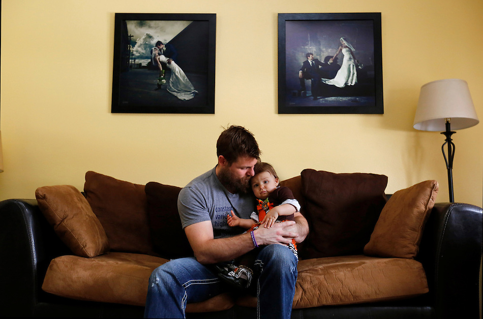 "Nate Yoho cradles his daughter Caralyn under wedding day photographs of himself and wife, Laura, in his Grimes home. Caralyn turns one year old on November 26.  She was born by surrogate after Laura died of cancer.  ""She's a joy. Laura wanted to be here for her, and that's pretty heavy on me. I take my responsibility as a father very seriously,"" he says. (Christopher Gannon/The Register)"