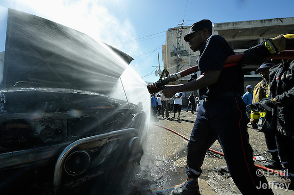 Fire fighters extinguish a fire in a car outside a Catholic mass in Port-au-Prince that marked the one-year anniversary of the January 12, 2010, earthquake that devastated Haiti. The car, which belongs to Father Allan Francois, was set afire by protestors upset about the government's management of the quake recovery. Held in the shadows of the ruins of the city's Catholic cathedral, the Mass was one of many special observances held throughout the Caribbean nation...