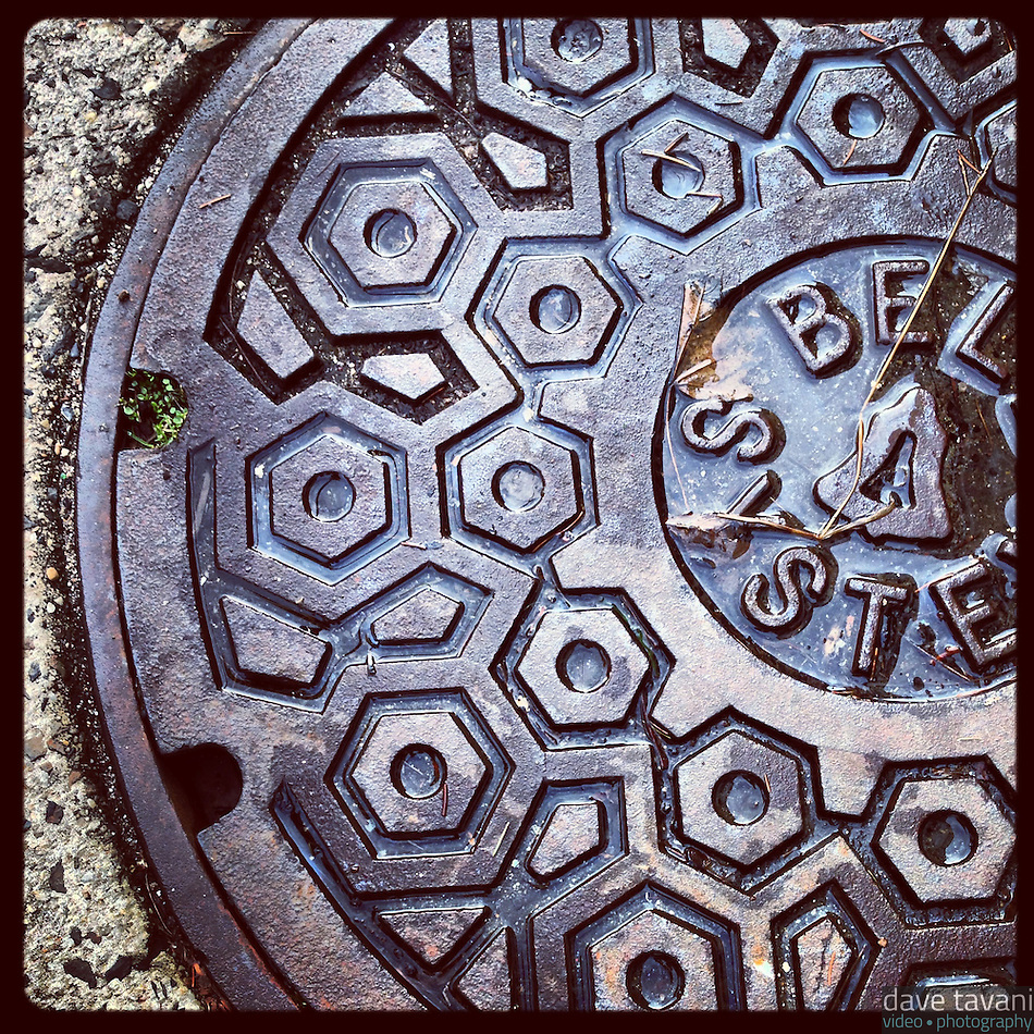 The sun peeked out of the clouds for a few minutes in the afternoon lighting up the tiny puddle in this manhole cover on Pomona Street in Germantown, January 29, 2013. (Dave Tavani)