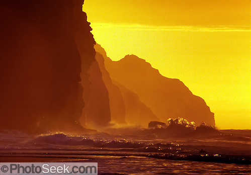 Waves crash at sunset on Kalalau Beach, Na Pali Coast, Kauai, Hawaii, USA.