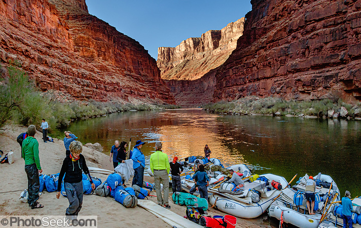 """Sunrise light spotlights a wall in Marble Canyon on day 2 of 16, where we breakfasted at Twentymile Camp at Colorado River Mile 20.2 in Grand Canyon National Park, Arizona, USA. Marble Canyon runs from Lees Ferry at River Mile 0 to the confluence with the Little Colorado River at Mile 62, which marks the beginning of the Grand Canyon. Although John Wesley Powell knew that no marble was found here when he named Marble Canyon, he thought the polished limestone looked like marble. In his words, """"The limestone of the canyon is often polished, and makes a beautiful marble. Sometimes the rocks are of many colors – white, gray, pink, and purple, with saffron tints."""" Multiple overlapping photos were stitched to make this panorama. For this photo's licensing options, please inquire at PhotoSeek.com. . (© Tom Dempsey / PhotoSeek.com)"""