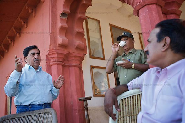 At the senior government guesthouse of Jogi Mahal a day before the planned relocation of a tiger from Rantambore to Sariska, R.N. Mehrotra (left), Chief Wildlife officer for Rajasthan, discusses strategy with Rajpal Singh, Member of the Rajasthan Tiger Task Force (right) and Divisional Forest officer R.S. Shekhawat (drinking tea)...Sariska National Park in Rajasthan was once home to dozens of tigers but by 2005 poaching had resulted in their complete eradication. Recognising the urgent need for intervention, the Indian and Rajasthan-state governments began the reintroduction of tigers into Sariska. Two cats were airlifted 200 km from Ranthambore National Park in June 2008. On November 5th an attempt to relocate a third tiger was postponed until later in the month. This relocation strategy is certainly an important part of the tiger conservation effort but many, including those like Dharmendra Khandal of the NGO Tiger Watch, argue that it will never be entirely successful without properly confronting the three essential issues that threaten tiger populations: poaching, habitat loss and the hunting of prey-base animals. In turn, these three issues cannot be addressed without acknowledging the malign influence of caste, poverty and poor administrative accountability. Poaching is almost exclusively undertaken by extremely poor and marginalised groups, including the Mogia caste who, without education, land and access to credit have limited alternative means of income. Many in the Mogia community also hunt bush meat for both their own consumption and to sell to others. This results in a depletion of the prey-base upon which tigers feed. Encroachment and grazing by those including the Gujar people who raise dairy herds, have led to habitat loss in Sariska and other parks. To properly tackle the problem of hunting and encroachment, the government must provide alternative livelihoods for marginalised groups and relocate them to viable land before - rather than after - the re (Tom Pietrasik)