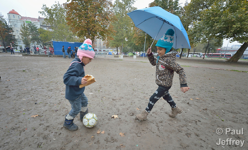 Four-year old Mashad kicks the ball to his 7-year old sister, Farah, in a city park in Belgrade, Serbia. They are refugees from Syria, and with their family fled that nation for western Europe. This park has filled with refugees from several countries stopping over on their way to Germany, Sweden, Holland, and elsewhere. Parental consent obtained. (Paul Jeffrey)