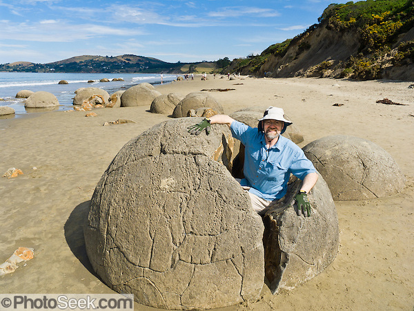 South Pacific Ocean waves released the spherical Moeraki Boulders onto Koekohe Beach, between Moeraki and Hampden on the Otago coast, South Island, New Zealand. These ancient concretions grew 2 meters (6 feet) in diameter over 4 to 5.5 million years from marine mud (Moeraki Formation mudstone) near the surface of the Paleocene sea floor. After the concretions formed, large cracks (septaria) formed and filled with brown calcite, yellow calcite, and small amounts of dolomite and quartz when a drop in sea level allowed fresh groundwater to flow through the enclosing mudstone. (© Carol Dempsey / PhotoSeek.com)