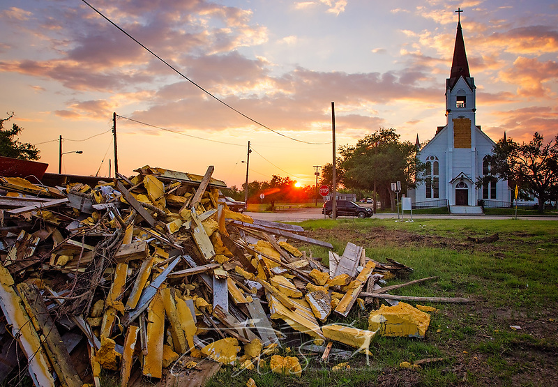 The sun sets on South Alamo Street, Oct. 1, 2017, in Refugio, Texas. Our Lady of Refuge Catholic Church, in the background, sustained minor damage when Hurricane Harvey struck the town as a category four storm in late August, but other structures were completely demolished. The town is slowly recovering thanks to the grit and determination of the townspeople. (Photo by Carmen K. Sisson) (Carmen K. Sisson/Cloudybright)