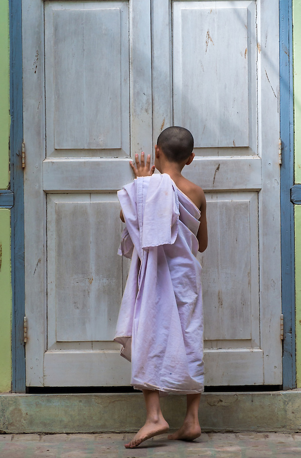 MANDALAY, MYANMAR - CIRCA DECEMBER 2013: Novice closing a door in a monastery  in Amarpura (Daniel Korzeniewski)
