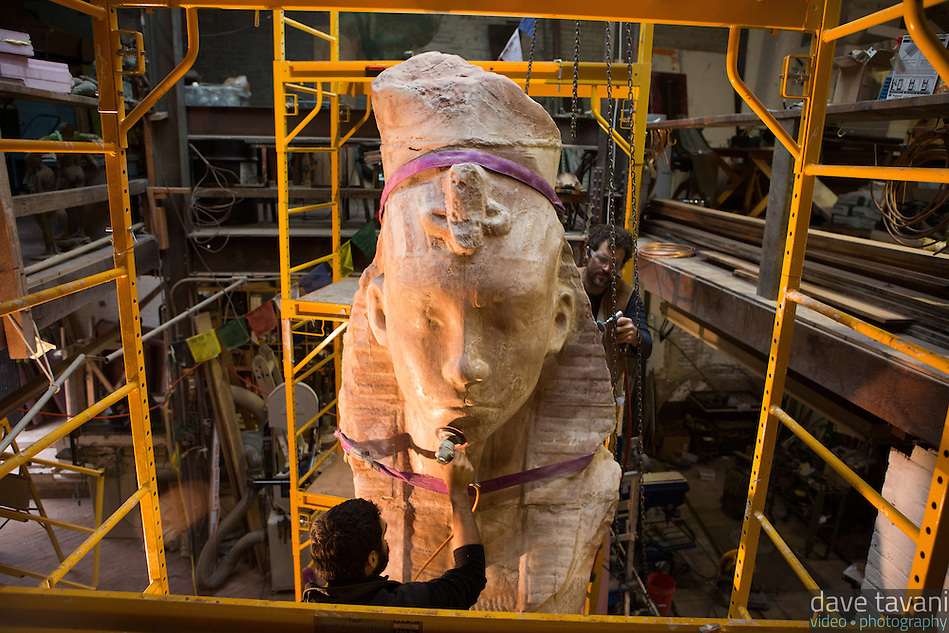 """Miguel Antonio Horn and Joel Erland use grinders to bring out the texture on Horn's sculpture """"Colossus,"""" a four meter statue of King Tutankhamen on the morning of November 1, 2013. (Dave Tavani)"""