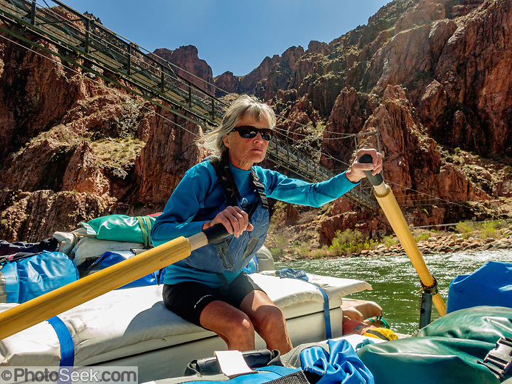 Arizona Raft Adventures (AZRA) trip leader Lorna Corson rows under Bright Angel Bridge (aka Silver Bridge). Built in the late 1960s, the Silver Bridge supports hikers and the transcanyon water pipeline across the Colorado River, connecting the Bright Angel Trail from the South Rim to Phantom Ranch and the North Rim. Hikers only (no mules) may cross this narrow suspension bridge. Five-hundred-thousand gallons of water a day are piped from Roaring Springs near the North Rim down Bright Angel Canyon through Phantom Ranch, across the Colorado River, and then pumped up to provide almost all of the water to the South Rim tourist area. Day 6 of 16 days rafting 226 miles down the Colorado River in Grand Canyon National Park, Arizona, USA. For this photo's licensing options, please inquire at PhotoSeek.com. . (© Tom Dempsey / PhotoSeek.com)