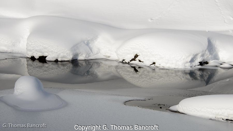 The snow bank reflected perfectly in the mirror like creek. (G. Thomas Bancroft)