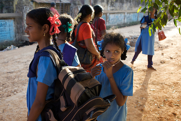 On a weekly visit, Krishnamurthy (not in photo) collects from school his three daughters attending Cuddalore's Government Girls High School. L to R foreground: Sivapriya (age 14). Anjalakshi (age 10)...The five Krishnamurthy sisters from Pudupettai were placed in the Government Home for Tsunami Children in Cuddalore, Tamil Nadu when they lost their mother to the 2004 tsunami. Their father, Krishnamurthy, had decided he could no longer provide day-to-day care for his daughters. Krishnamurthy later remarried. The Krishnamurthy sisters now range in age from eight to sixteen...The four younger sisters are still at the Governement home (or orphanage). In summer 2009, Sivaranjini, the eldest aged sixteen, failed her 10th Standard exams and had to drop out of school so leaving her not eligible for care at the Government home. She is now living with her father and his new wife Nagamalli's house 30km away in Pudupettai. Krishnamurthy is intending that Sivaranjini marry a second cousin in 2010. ..Krishnamurthy visits the Government orphanage once a week to see his four younger daughters. Nagamalli is popular with all five sisters. She provides them attention when they are together and is genuinely interested in their well-being. Sivapriya remains close to her paternal aunt Kamasala with whom she used to live in the fishing village of Thazanguda. Kamasala visits Sivapriya at the orphanage every fortnight. The sisters return to their father's home for festivals including Diwali and the Pudupettai village temple festival...According to Revathi, the staff member in charge at the Government home, the absence of the elder Sivaranjini has had the effect of making the remaining four sisters still at the home increasingly independent. For instance, where they used to all sleep together the girls now sleep in different dormitories. The eldest of these four, fourteen year-old Sivapriya has adopted some of the responsibilities of her elder sisters including coordinating clothes washing a (Tom Pietrasik)