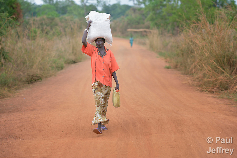 Asanta Jantana walks along a road in Kotobi, South Sudan, carrying some of the food and non-food items she received during a distribution of aid to displaced families. She is one of thousands who were displaced by political violence that broke out in December 2013 and quickly fractured regions of the young nation along ethnic and tribal lines. Jantana fled Juba with her seven children for this village, where she moved in with a brother. Yet she hasn't had enough food for her whole family, so she sent four of her children to live with another relative. She hasn't heard from her husband, a soldier, since the fighting began. Finn Church Aid, a member of the ACT Alliance, provided materials for this aid distribution. The ACT Alliance is providing a variety of services to internally displaced families throughout the country. (Paul Jeffrey)
