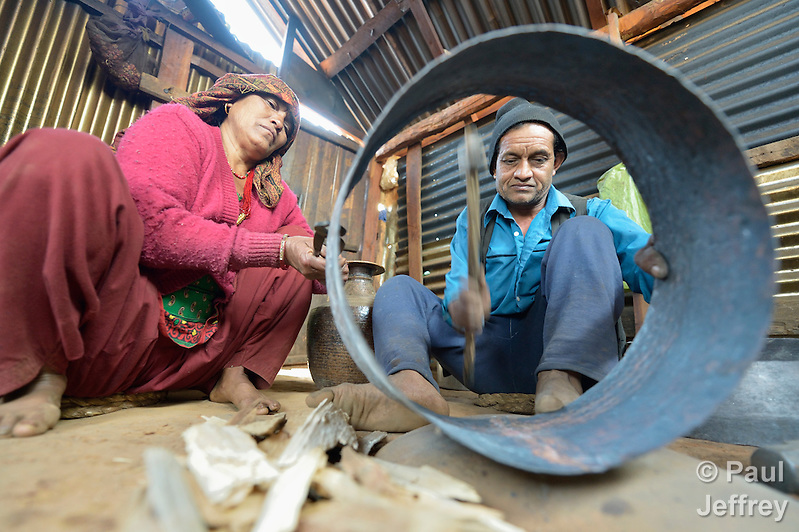 Mithe, a blacksmith in Dhawa, a village in the Gorkha District of Nepal, works on a metal pot with assistance from his wife, Mankumari. In Nepal's caste system, blacksmiths are near the bottom, but helping them recover their livelihoods after a 2015 earthquake ravaged their community has been a priority for some aid agencies. (Paul Jeffrey)