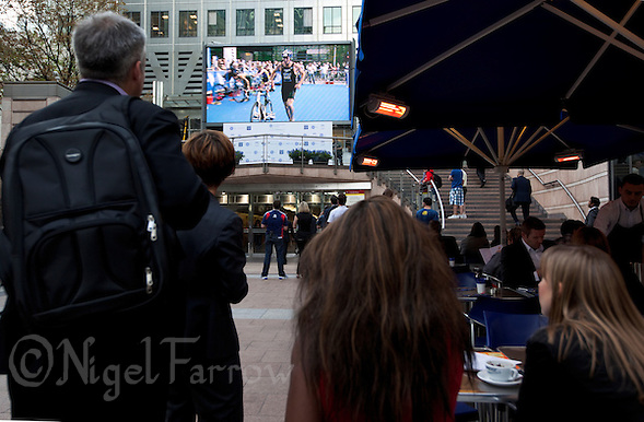 30 JUN 2011 - LONDON, GBR - Spectators watch events unfold on a TV screen during the GE Canary Wharf Triathlon .(PHOTO (C) NIGEL FARROW) (NIGEL FARROW/(C) 2011 NIGEL FARROW)