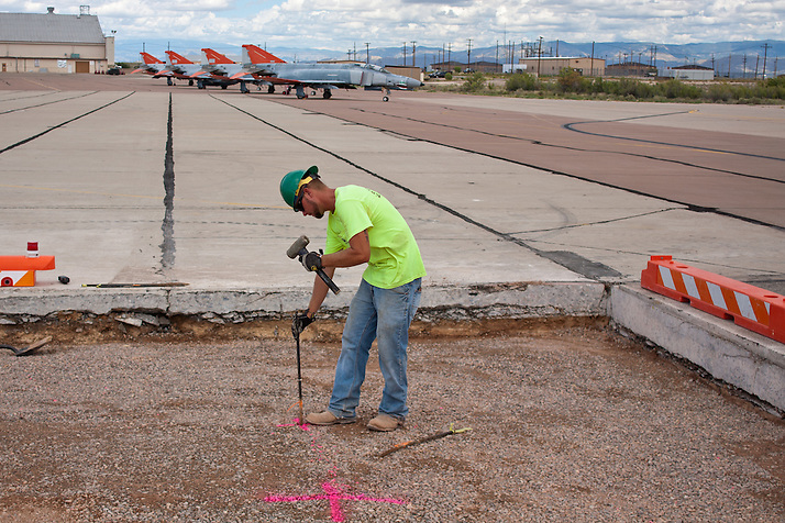 Laborer Jaysen Raymond hammers down a stake as construction crews at work building new runways at Holloman Air Force Base in Otero County. HAFB received over $21 million to upgrade various facilities as part of the Recovery and Reinvestment Act. (Steven St. John)