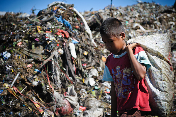 Idris, 13, searching for plastic and metal to recycle amongst newly dumped waste at the 'Trash mountain', Makassar, Sulawesi, Indonesia. (Matthew Oldfield)