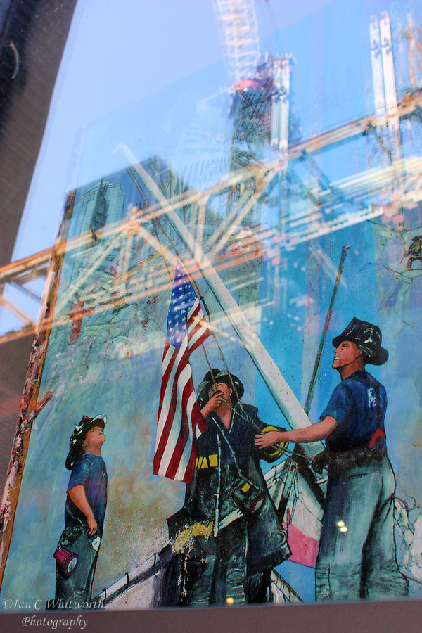 A view of a picture of the firefighters in the window at ground zero memorial with the new construction at the World Trade Center site caught in the reflection (Ian C Whitworth)
