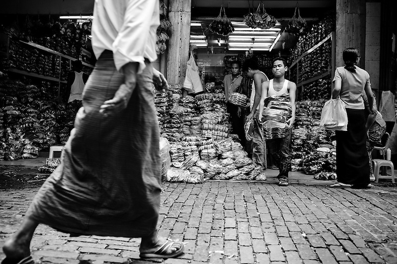 A man in a tradional Burmese longyi passes by a shop with a large stock of sandals on offer, in the Scott market in Yangon. (Quinn Ryan Mattingly)