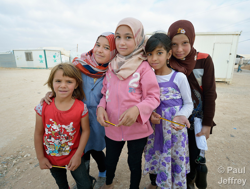 Girls pose on their walk to school in the Zaatari refugee camp near Mafraq, Jordan. Established in 2012 as Syrian refugees poured across the border, the camp held more than 80,000 refugees by early 2015, and was rapidly evolving into a permanent settlement. The ACT Alliance provides a variety of services to refugees living in the camp. (Paul Jeffrey)