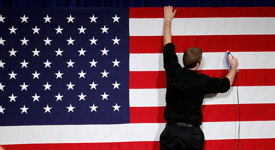 Stage hand RICHIE BEANAN of Milwaukee, Wisconsin irons the American Flag while preparing the Iowa caucus rally site for Republican Presidential hopeful MITT ROMNEY on Tuesday, January 3, 2012 in Des Moines, Iowa. (Christopher Gannon/Zuma Press)