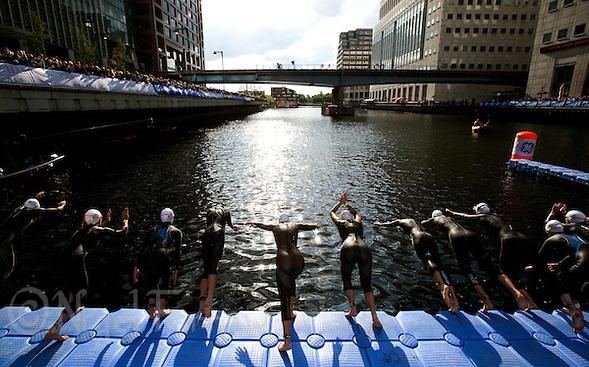 30 JUN 2011 - LONDON, GBR - Competitors dive into the water for the start of the women's super sprint elimination round at the GE Canary Wharf Triathlon (PHOTO (C) NIGEL FARROW) (NIGEL FARROW/(C) 2011 NIGEL FARROW)