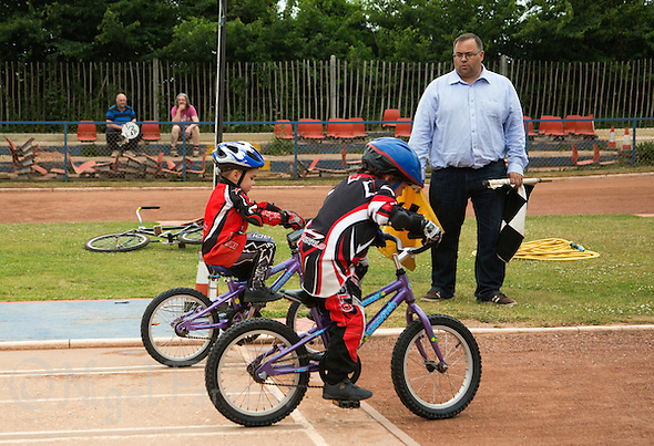 12 JUN 2015 - IPSWICH, GBR - Riders, watched by Ipswich Cycle Speedway Club chairman Jamie Goldsmith, practice starts during an academy training session at Whitton Sports and Community Centre in Ipswich, Suffolk, Great Britain (PHOTO COPYRIGHT © 2015 NIGEL FARROW, ALL RIGHTS RESERVED) (NIGEL FARROW/COPYRIGHT © 2015 NIGEL FARROW : www.nigelfarrow.com)