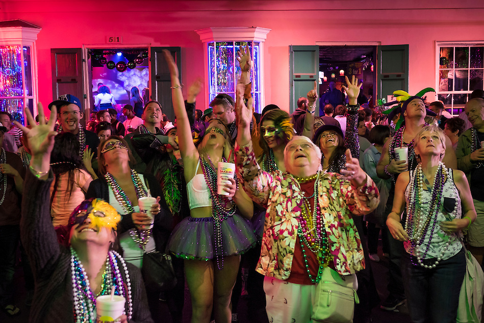 NEW ORLEANS - CIRCA FEBRUARY 2014: People looking up and raising hands to get beads in Bourbon Street during Mardi Gras celebrations in the French Quarter in New Orleans (Daniel Korzeniewski)