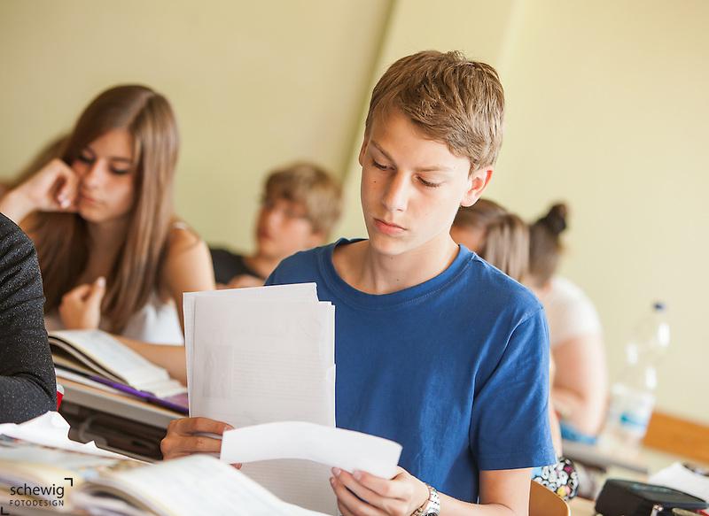 Österreich, Schüler Unterlagen sortierend, konzentriert (dieter schewig)