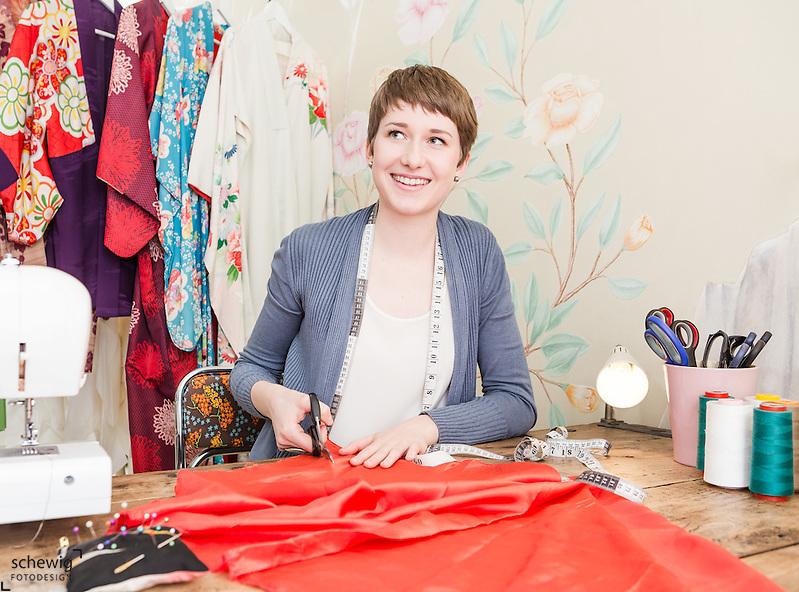 Junge Frau Stoff zuschneidend am Tisch ihres Workshops, Wien, Österreich, Jungunternehmerin im Kreativbereich, Mode oder Trend DIY als bewusste Freizeitgestaltung (Dieter Schewig)