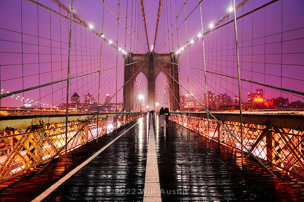Brooklyn Bridge in New York glows at twilight during a storm