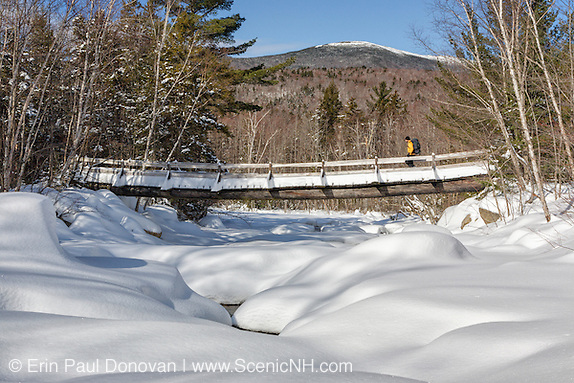 Hiker crossing footbridge along the Thoreau Falls Trail in the Pemigewasset Wilderness of New Hampshire during the winter months. This bridge is in an area referred to as North Fork Junction and crosses the East Branch of the Pemigewasset River. Just beyond this bridge was the location of a timber trestle of the old East Branch & Lincoln railroad (1893-1948).