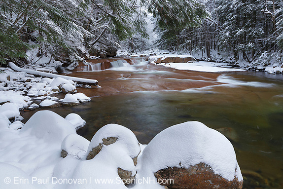 The Pemigewasset River near the Flume Visitor Center in Franconia Notch State Park in Lincoln, New Hampshire covered in snow on a cloudy autumn day.