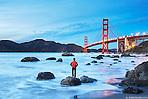 A man stands on a rock at Marshall's Beach admiring the Golden Gate Bridge in San Francisco, California. (Seth K Hughes)
