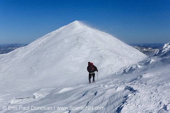 A winter hiker heading north on the Appalachian Trail in extreme weather conditions during the winter months in the White Mountains, New Hampshire USA. Mount Madison is in the background.