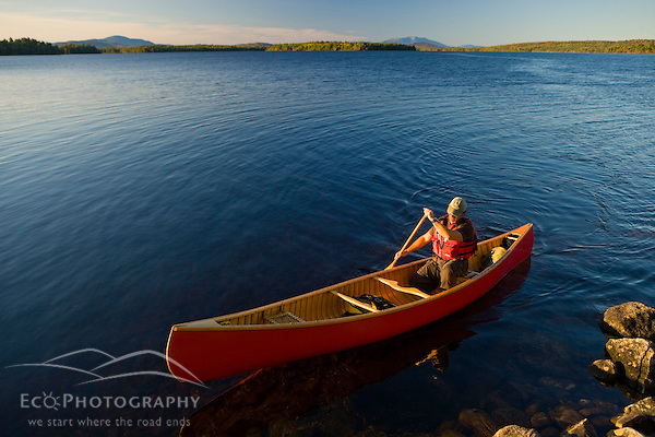A man paddles his canoe on Seboeis Lake near Millinocket, Maine. Mount Katahdin is in the distance. (MR) (Jerry and Marcy Monkman)