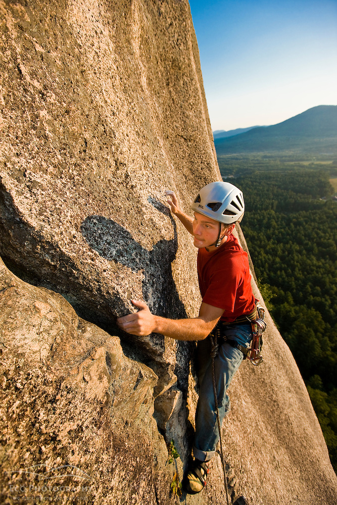 A man rock climbing near the top of Cathedral Ledge.  Echo Lake State Park in North Conway, New Hampshire.  White Mountains. (Jerry and Marcy Monkman)