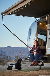 A woman and her dog sit near the doorstep of thier Airstream trailer while camping in the desert of Anza Borrego, California. (Seth K Hughes)