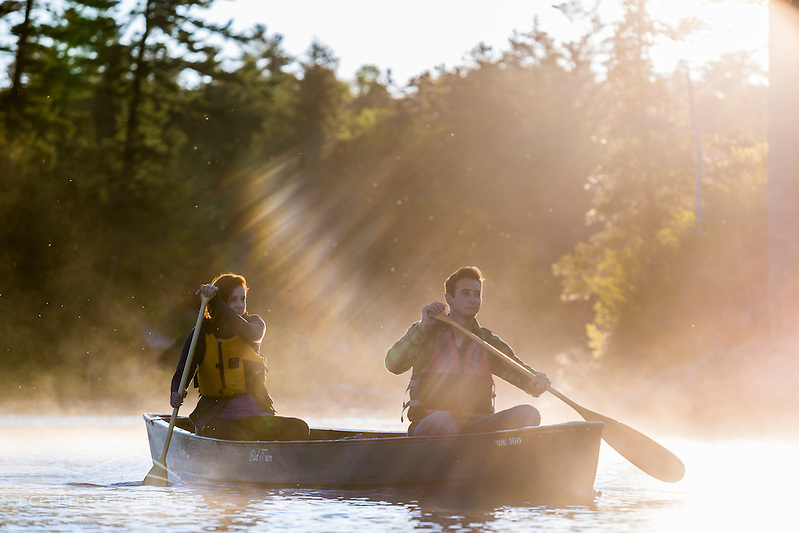 A young couple paddles a canoe through morning mist on Long Pond in Maine's north woods. Near Greenville, Maine. (Jerry and Marcy Monkman)