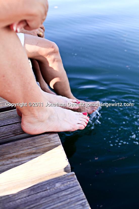 The bare legs and feet of three people sitting on a dock. (Jonathan Gewirtz)
