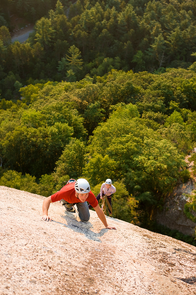 A couple rock climbing near the top of Cathedral Ledge.  Echo Lake State Park in North Conway, New Hampshire.  White Mountains. (Jerry and Marcy Monkman)