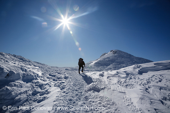A hiker on the Appalachian Trail in the Presidential Range of the White Mountains, New Hampshire during the winter months. Mount Monroe is in the background.