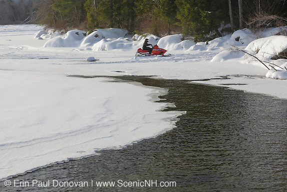A snowmobile makes his way off the lake and into Wellington State Park during the winter months.. Located in Bristol, New Hampshire USA.