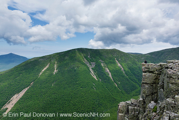 A hiker sitting on the summit of Bondcliff in the Pemigewasset Wilderness of New Hampshire during the summer months. West Bond is on the other side of Hellgate Ravine.
