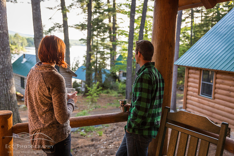 A young couple enjoy an evening on the porch of a cabin at the Appalachian Mountain Club's Gorman Chairback Lodge. Long Pond. Near Greenville, Maine. (Jerry and Marcy Monkman)