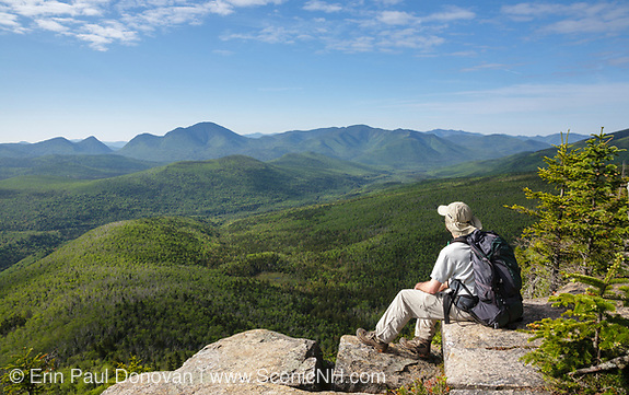 A hiker takes in the view of the Pemi Wilderness from the summit of Zeacliff during the summer months. This view is located along the Appalachian Trail in the White Mountains of New Hampshire. And can be visited by Appalachian Trail through hikers.
