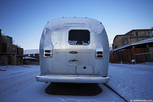 An Airstream trailer sits parked covered in snow and ice on a cold residential street in Denver, Colorado. (Seth K Hughes)