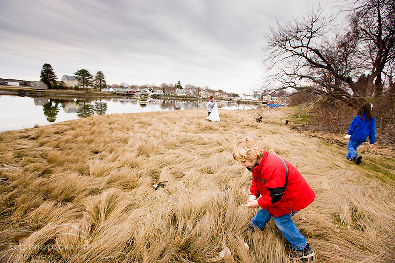 A boy picking up trash as part of a beach clean-up sponsored by the Blue Ocean Society on Pierce Island in Portsmouth, New Hampshire. (Jerry and Marcy Monkman)