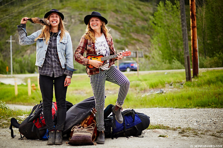 Two spirited young women stand alongside a highway hitchhiking on the Klondike Highway in Yukon Territory, Canada. (Seth K Hughes)
