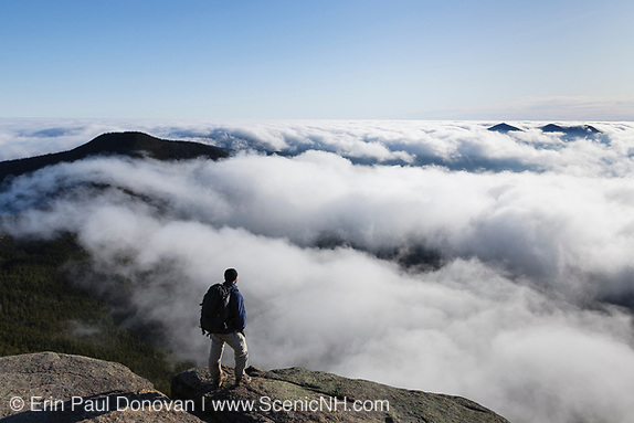 A hiker takes in the view of undercast from the summit of Mount Osceola in the White Mountains, New Hampshire USA (Erin Paul Donovan)