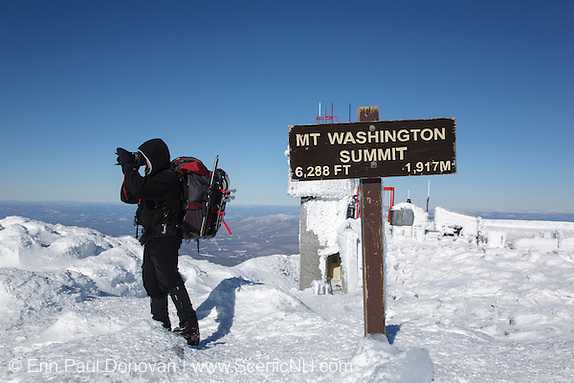 Cold camera batteries, a hiker photographs around the summit of Mount Washington during the winter months in the White Mountains, New Hampshire.